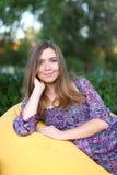 Retrato de la muchacha linda que se sienta en silla y que sonríe en fotografía Fotos de archivo libres de regalías