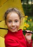 Retrato de la muchacha linda sonriente en chaqueta roja con el paraguas al aire libre Imágenes de archivo libres de regalías