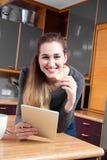 Retrato de la muchacha magnífica feliz que sostiene una tableta en casa Imágenes de archivo libres de regalías