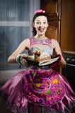 Retrato de la muchacha modela divertida sincera encantadora en un delantal del vestido que tiene torta sabrosa que cuece sonrient Imagen de archivo