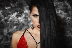 Retrato de la muchacha modelo morena hermosa y de moda con maquillaje brillante y con los pendientes grandes en ropa interior roj imagenes de archivo