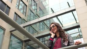 Retrato de la muchacha moderna con el teléfono cerca del rascacielos almacen de video