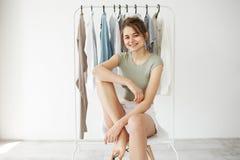 Retrato de la muchacha morena bonita joven que sonríe mirando la cámara que se sienta en silla sobre guardarropa de la suspensión Imágenes de archivo libres de regalías