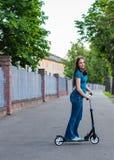 Retrato de la muchacha morena del adolescente joven con el pelo largo que conduce la vespa en la calle de la ciudad fotografía de archivo