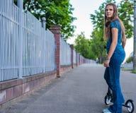 Retrato de la muchacha morena del adolescente joven con el pelo largo que conduce la vespa en la calle de la ciudad imágenes de archivo libres de regalías