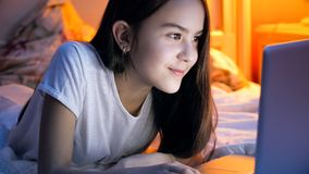 Retrato de la muchacha morena hermosa con el ordenador portátil en la cama Foto de archivo