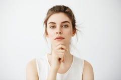 Retrato de la muchacha morena hermosa joven que mira la cámara que presenta la cara conmovedora sobre el fondo blanco Fotos de archivo libres de regalías