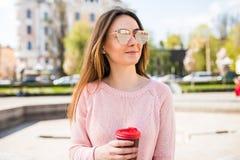Retrato de la muchacha morena hermosa que camina abajo de la calle que mantiene la bebida para llevar una sonrisa de la mano Esce Imagen de archivo libre de regalías