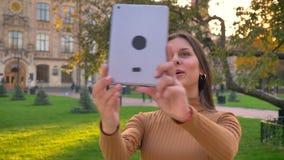 Retrato de la muchacha morena hermosa que habla en videochat y que muestra el fondo verde del parque usando su tableta almacen de metraje de vídeo