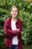 Retrato de la muchacha morena hermosa que presenta en jardín con los manzanos crecientes Foto de archivo libre de regalías