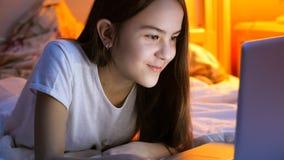 Retrato de la muchacha morena hermosa que usa el ordenador portátil en cama en la noche Foto de archivo libre de regalías