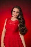 Retrato de la muchacha morena joven en un vestido rojo en fondo rojo Foto de archivo
