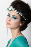 Retrato de la muchacha morena joven en vestido de la turquesa con la flor d imagen de archivo