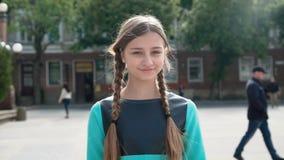 Retrato de la muchacha morena joven que considera adelante la cámara y la sonrisa metrajes