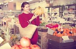 Retrato de la muchacha morena que compra plátanos maduros en supermercado Fotografía de archivo libre de regalías