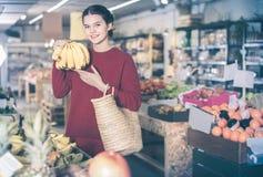 Retrato de la muchacha morena que compra plátanos maduros en supermercado Imagenes de archivo