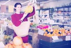 Retrato de la muchacha morena que compra plátanos maduros en supermercado Imagen de archivo