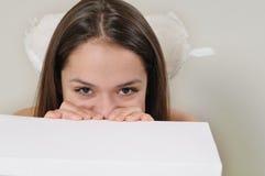 Retrato de la muchacha muy tímida linda del ángel que oculta detrás de una caja blanca Fotos de archivo libres de regalías
