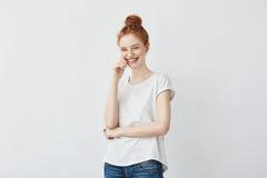 Retrato de la muchacha pecosa elegante joven que ríe con la mano en la mejilla que mira la cámara Copie el espacio Aislado en bla Imagenes de archivo