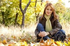 Retrato de la muchacha pelirroja en el parque del otoño Imágenes de archivo libres de regalías