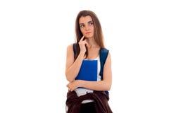 Retrato de la muchacha pensativa joven del estudiante con la mochila azul y de las carpetas para los cuadernos aislados en el fon Imagen de archivo libre de regalías