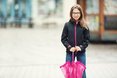 Retrato de la muchacha pre-adolescente joven hermosa feliz con el paraguas rosado debajo de la lluvia Imagen de archivo