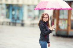 Retrato de la muchacha pre-adolescente joven hermosa feliz con el paraguas rosado debajo de la lluvia Fotos de archivo