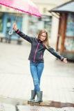 Retrato de la muchacha pre-adolescente joven hermosa feliz con el paraguas rosado debajo de la lluvia Imagenes de archivo