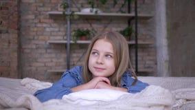Retrato de la muchacha preciosa del niño con los ojos azules que mienten en la almohada en cama en sitio almacen de video