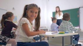 Retrato de la muchacha preciosa del principiante en el escritorio durante la lección de la educación en sala de clase en la escue almacen de metraje de vídeo