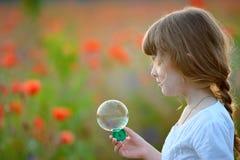 Retrato de la muchacha preciosa divertida del niño con las burbujas de jabón al aire libre Fotos de archivo libres de regalías