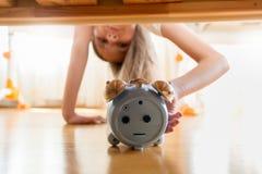 Retrato de la muchacha que alcanza para el despertador debajo de la cama Imágenes de archivo libres de regalías