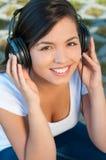 Retrato de la muchacha que escucha la música en los auriculares Imagen de archivo