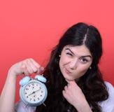 Retrato de la muchacha que señala en el reloj contra fondo rojo Imágenes de archivo libres de regalías