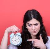 Retrato de la muchacha que señala en el reloj contra fondo rojo Fotografía de archivo libre de regalías