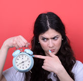 Retrato de la muchacha que señala en el reloj contra fondo rojo Fotos de archivo libres de regalías