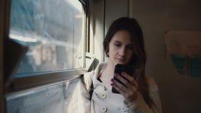 Retrato de la muchacha que se coloca en el tren y que usa smartphone El SMS que manda un SMS de la mujer joven y hojea Internet Foto de archivo libre de regalías