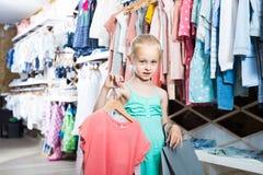 Retrato de la muchacha que se coloca en tienda de la ropa de los niños con b que hace compras Imagen de archivo