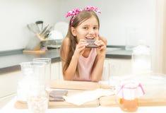 Retrato de la muchacha que se inclina en la tabla de cocina y que come el chocolate Imagen de archivo libre de regalías