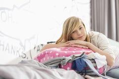Retrato de la muchacha que se relaja en la maleta que bombea en casa Foto de archivo