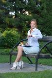 Retrato de la muchacha que se sienta en el banco Fotografía de archivo
