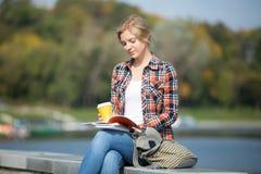Retrato de la muchacha que se sienta en la lectura del puente Foto de archivo libre de regalías