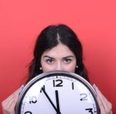 Retrato de la muchacha que sostiene el reloj enorme de la oficina contra fondo rojo Fotos de archivo