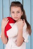 Retrato de la muchacha que sostiene la almohada en forma de corazón de la felpa Fotos de archivo libres de regalías