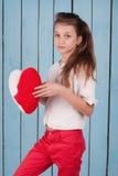 Retrato de la muchacha que sostiene la almohada en forma de corazón de la felpa Imagen de archivo