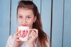 Retrato de la muchacha que sostiene una taza con el corazón en él Foto de archivo