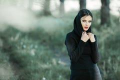 Retrato de la muchacha que tira de sus gastos indirectos de moda del suéter que se divierten Foto atmosférica al aire libre de la fotos de archivo