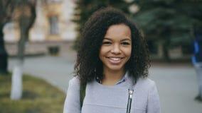 Retrato de la muchacha rizada del estudiante de la raza mixta que sonríe en cámara y que se ríe de la calle de la ciudad almacen de video