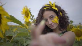 Retrato de la muchacha rizada hermosa que invita, espectador attrakting en el campo del girasol Color amarillo brillante conexi?n metrajes