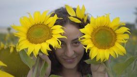 Retrato de la muchacha rizada hermosa que mira la cámara que sonríe cubriendo su cara con dos girasoles en el girasol almacen de metraje de vídeo